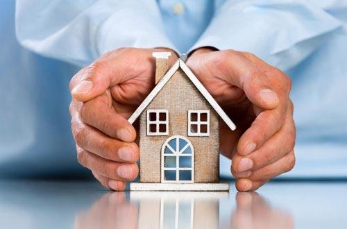 Haus wird von Händen geschützt