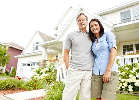 eine zufriedene Familie steht vor ihrem Haus